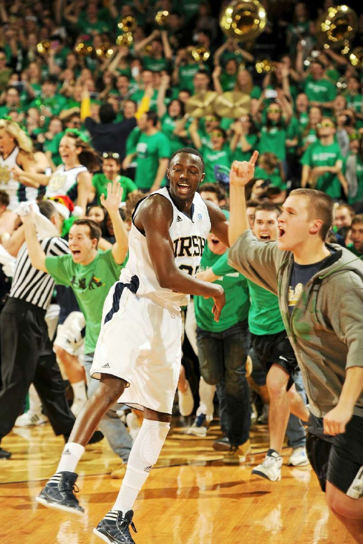 ASSOCIATED PRESS Notre Dame guard Jerian Grant throws the ball into the stands as fans rush the court following Notre Dame's 67-58 victory over Syracuse Saturday in South Bend, Ind.