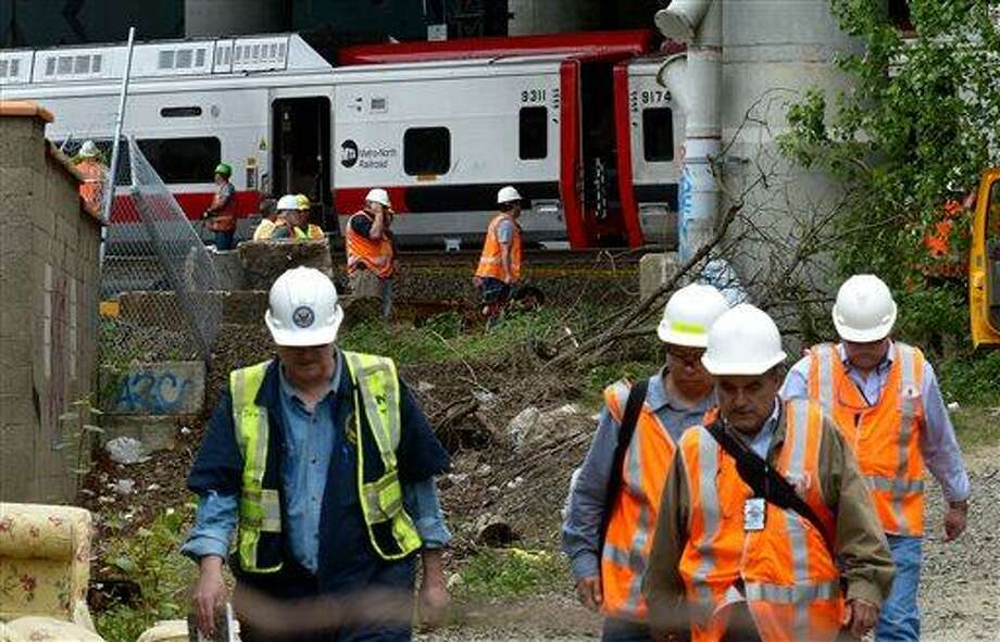 Metro-North Railroad officials tour the scene of the train derailment, Saturday, May 18, 2013 in Bridgeport, Conn. Officials described a devastating scene of shattered cars and other damage where two trains packed with rush-hour commuters collided in Connecticut, saying Saturday it's fortunate that no one was killed and that there weren't even more injuries. (AP Photo/Connecticut Post, Christian Abraham) MANDATORY CREDIT Photo: AP / Connecticut Post