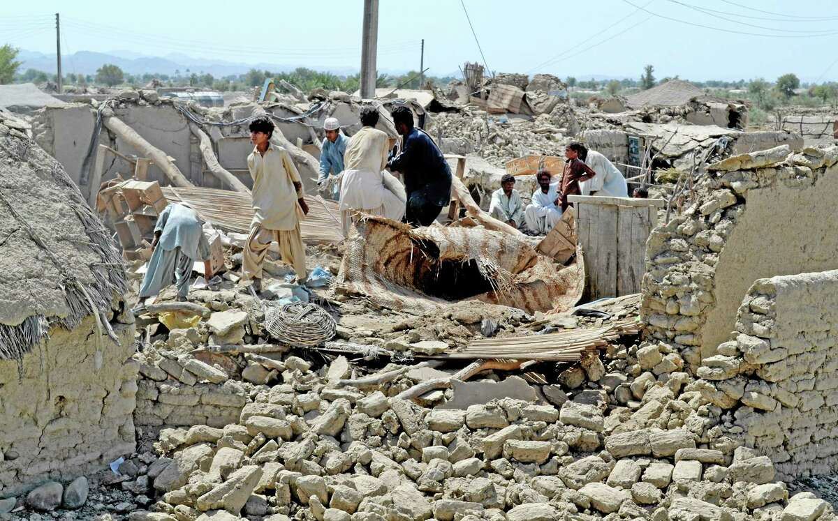Pakistani villagers look for belongings amid the rubble of their destroyed homes following an earthquake in the remote district of Awaran, Baluchistan province, Pakistan, Wednesday, Sept. 25, 2013. Rescuers struggled Wednesday to help thousands of people injured and left homeless after their houses collapsed in a massive earthquake in southwestern Pakistan Tuesday, Sept. 24, 2013, as the death toll rose to hundreds. (AP Photo/Arshad Butt)