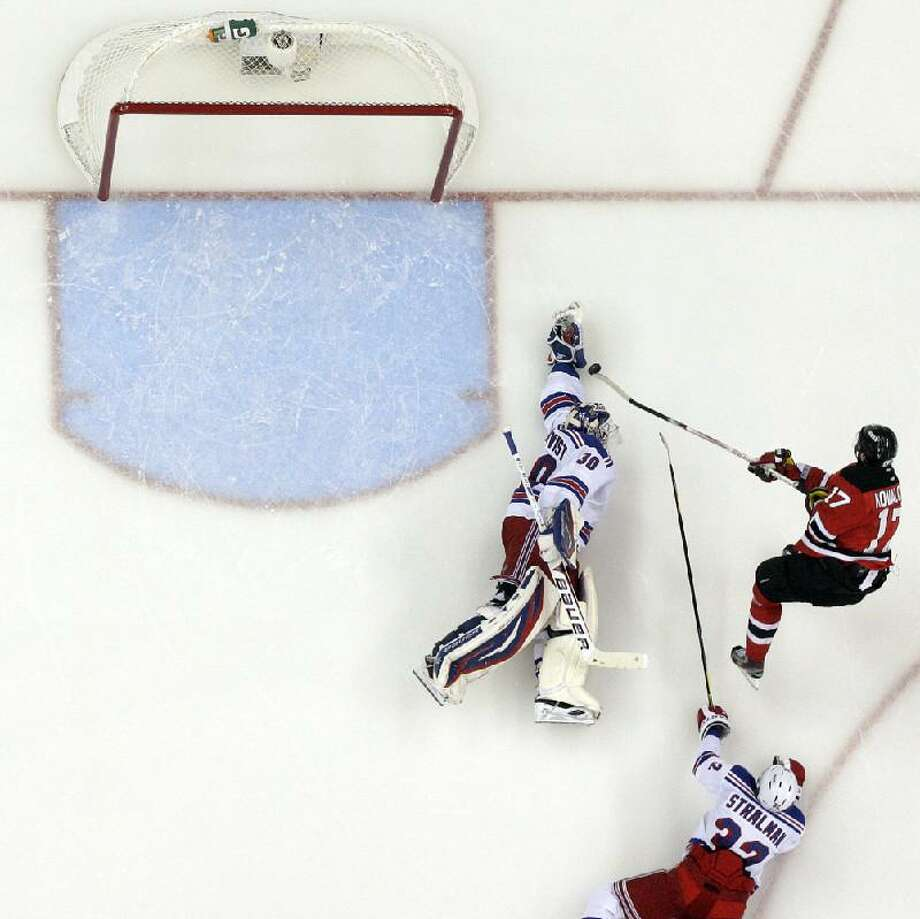 ASSOCIATED PRESS New York Rangers goalie Henrik Lundqvist, left, makes a stop on a shot by New Jersey Devils' Ilya Kovalchuk (17 as Rangers' Anton Stralman helps defend during the second period of Game 3 of a Stanley Cup Eastern Conference final series Saturday in Newark, N.J. The Rangers won 3-0 to take a 2-1 series lead.