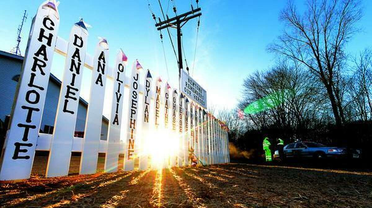 The memorial near the Sandy Hook firehouse is seen on Dec. 20 as the sun rises above the trees, illuminating parts of the memorial, and Connecticut State Troopers block of the entrance road to the Sandy Hook Elementary School. Staff photo by Tom Kelly IV
