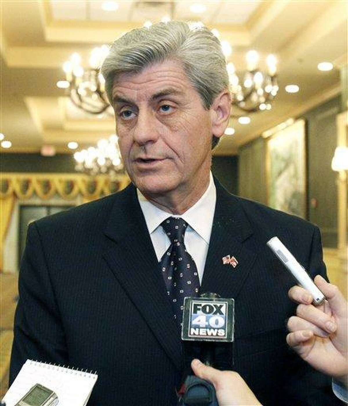 Mississippi Gov. Phil Bryant tells reporters he favors says some sort of limits on gubernatorial pardon powers as he walks to address members of the Mississippi Hospital Association Tuesday. Many in Mississippi favor a constitutional amendment that would allow a governor to single-handedly grant pardons only in cases in which there's clear evidence of innocence. Associated Press