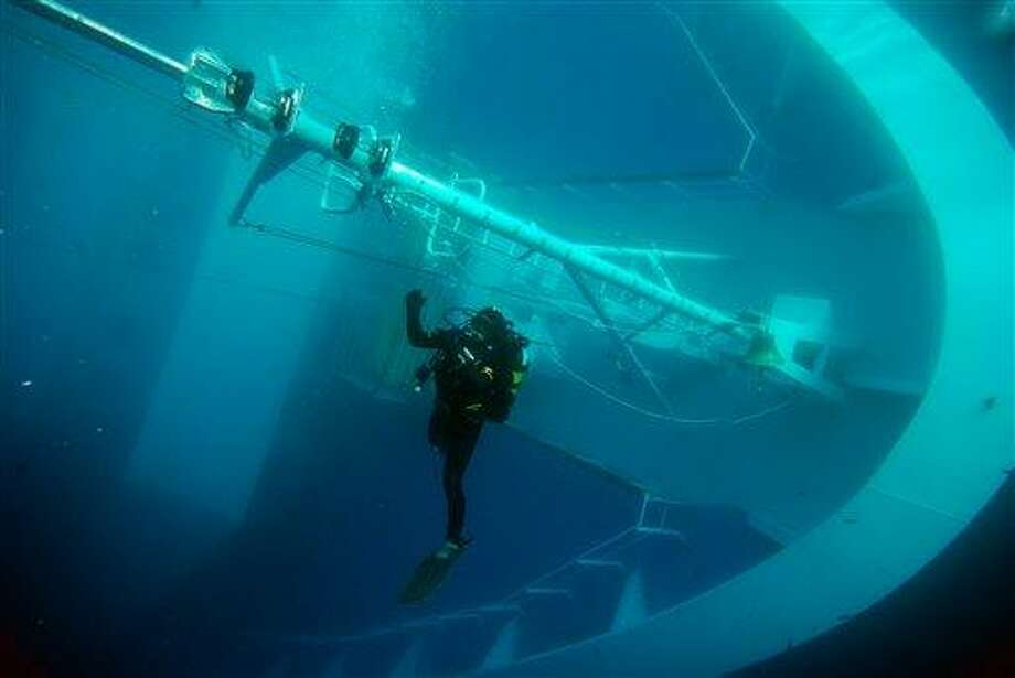 In this undated underwater photo released by Carabinieri (Italian paramilitary police) Friday, a  scuba diver swims next to the Costa Concordia cruise ship, off the tiny Giglio island, Italy. The $450 million Costa Concordia was carrying more than 4,200 passengers and crew when it slammed into well-marked rocks off the island of Giglio after the captain made an unauthorized diversion from his programmed route. The ship has been shifting on the rocks ocasionally, forcing the suspension of underwater searches.  Associated Press Photo: AP / Carabinieri
