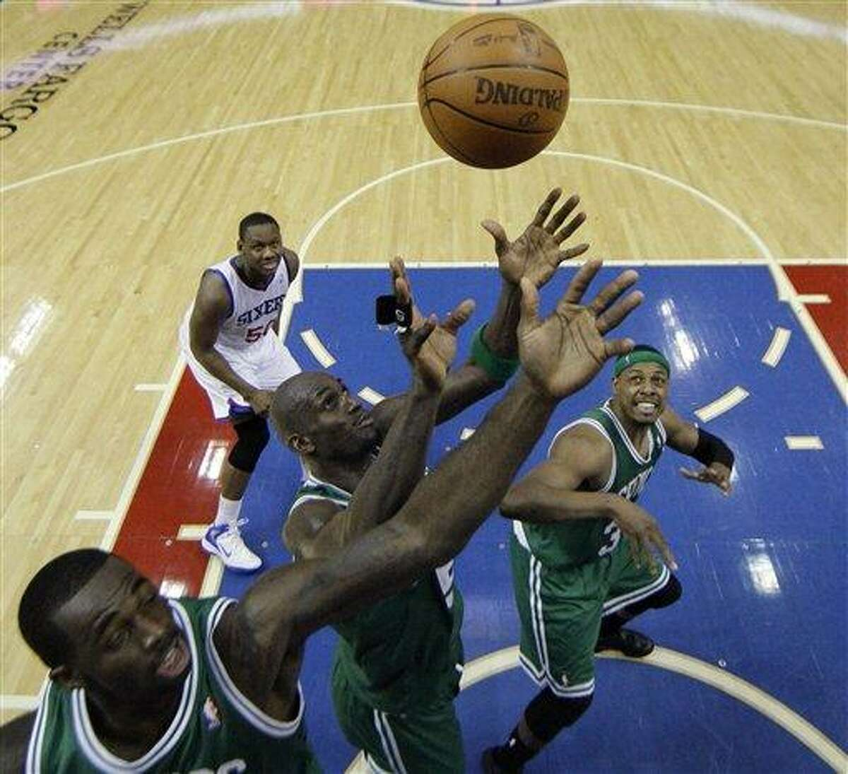 Boston Celtics' Brandon Bass, from left, Kevin Garnett and Paul Pierce chase down a rebound as Philadelphia 76ers' Lavoy Allen, top left, watches during the second half of Game 3 of an NBA basketball Eastern Conference semifinal playoff series, Wednesday, May 16, 2012, in Philadelphia. Boston won 107-91. (AP Photo/Matt Slocum)