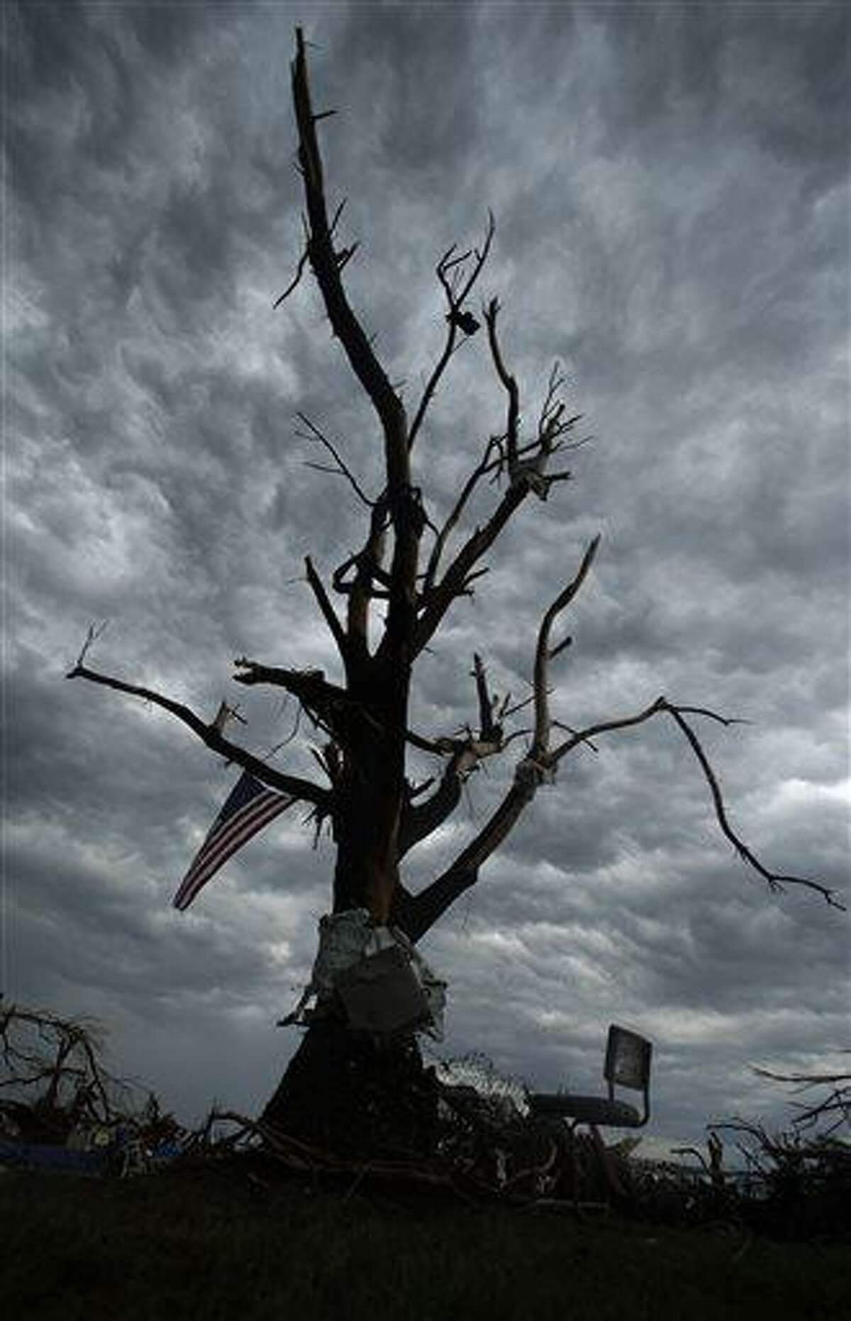 A flag hangs from tornado-ravaged tree Thursday, May 23, 2013, in Moore, Okla. Cleanup continues three days after a huge tornado roared through the Oklahoma City suburb, flattening a wide swath of homes and businesses. (AP Photo/Charlie Riedel)