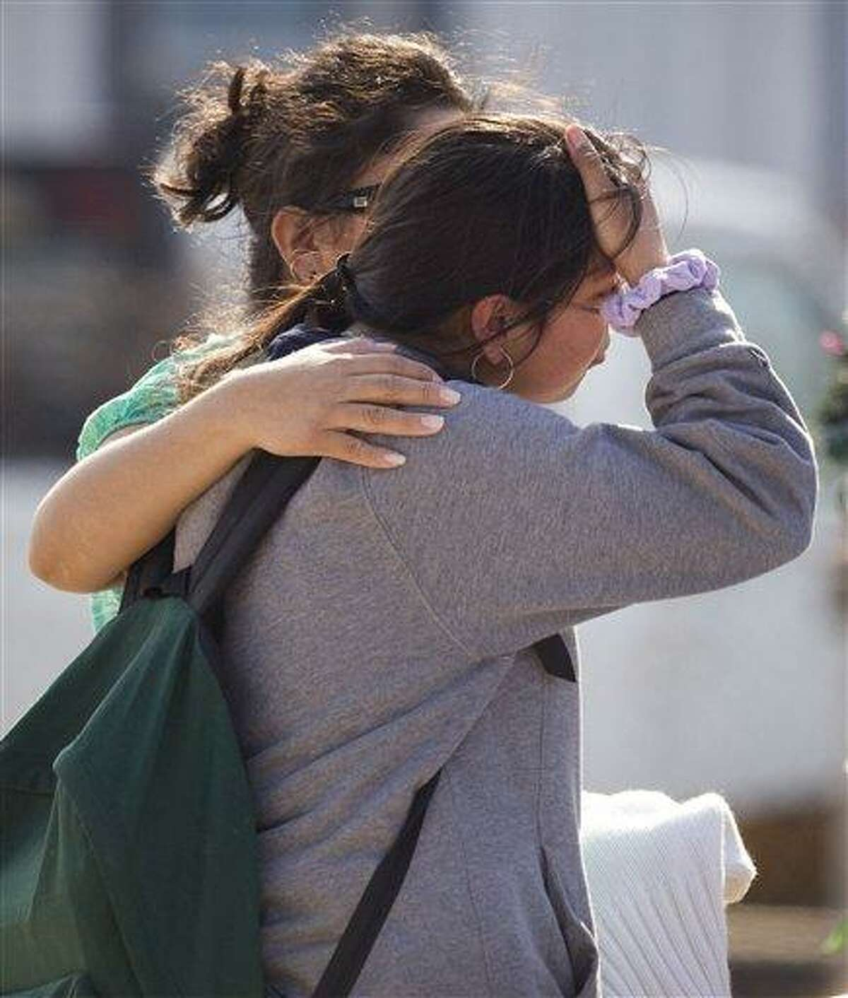 Ana Leal, left, embraces Lone Star College student Sabrina Cuellar after she was evacuated from the campus following a shooting at the north Harris County school Tuesday, Jan. 22, 2013, in Houston. The shooting wounded three people and sent students fleeing for safety as officials placed the campus on lockdown, officials said. (AP Photo/Houston Chronicle, Brett Coomer) MANDATORY CREDIT