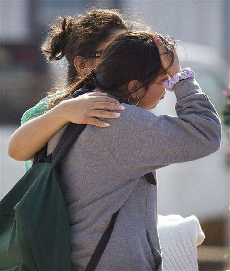 Ana Leal, left, embraces Lone Star College student Sabrina Cuellar after she was evacuated from the campus following a shooting at the north Harris County school Tuesday, Jan. 22, 2013, in Houston. The shooting wounded three people and sent students fleeing for safety as officials placed the campus on lockdown, officials said. (AP Photo/Houston Chronicle, Brett Coomer) MANDATORY CREDIT Photo: ASSOCIATED PRESS / 2013 Houston Chronicle2013