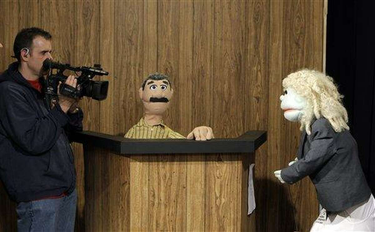 Cameraman Dave Spangler, left, films puppets reenacting testimony in a county corruption trial at the WOIO-TV studios in Cleveland Thursday, Jan. 19, 2012. The station uses the puppets performing as witnesses, reporters and jurors to detail the corruption trial against former Cuyahoga county commissioner Jimmy Dimora, which began last week in federal court in Akron. (AP Photo/Mark Duncan)