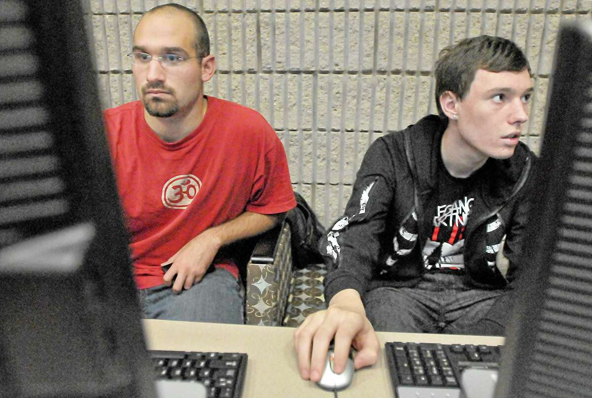 Members of the Middlesex Community College Computer Club Nathan Breininger, a Management Information Systems major from Durham, at left and Ethan Damuck, a Computer Science major East Haddam install drivers to desktop computers which the club will donate to the Ryan Woods Autism Foundation after-school program in Middletown. Catherine Avalone - The Middletown Press