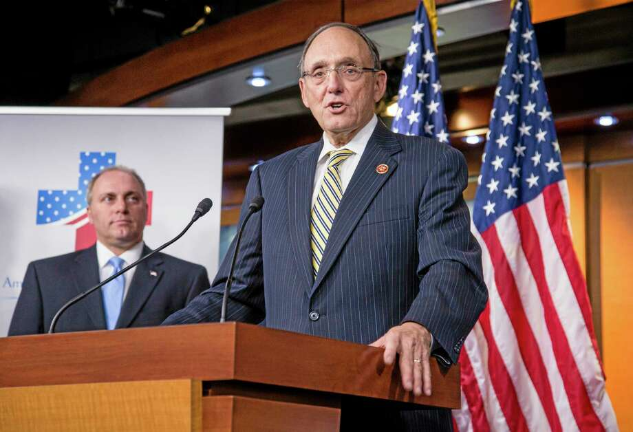 Rep. Phil Roe, R-Tenn., center, speaks as  Rep. Steve Scalise, R-La., chairman of the Republican Study Committee, listens as members of the House Republican Study Committee, gather to announce the American Health Care Reform Act, the group's legislation to replace the Affordable Care Act, popularly known as Obamacare, on Capitol Hill in Washington, Wednesday, Sept. 18, 2013. Roe is a medical doctor by training and chairman of the RSC's Health Care Working Group. (AP Photo/J. Scott Applewhite) Photo: AP / AP