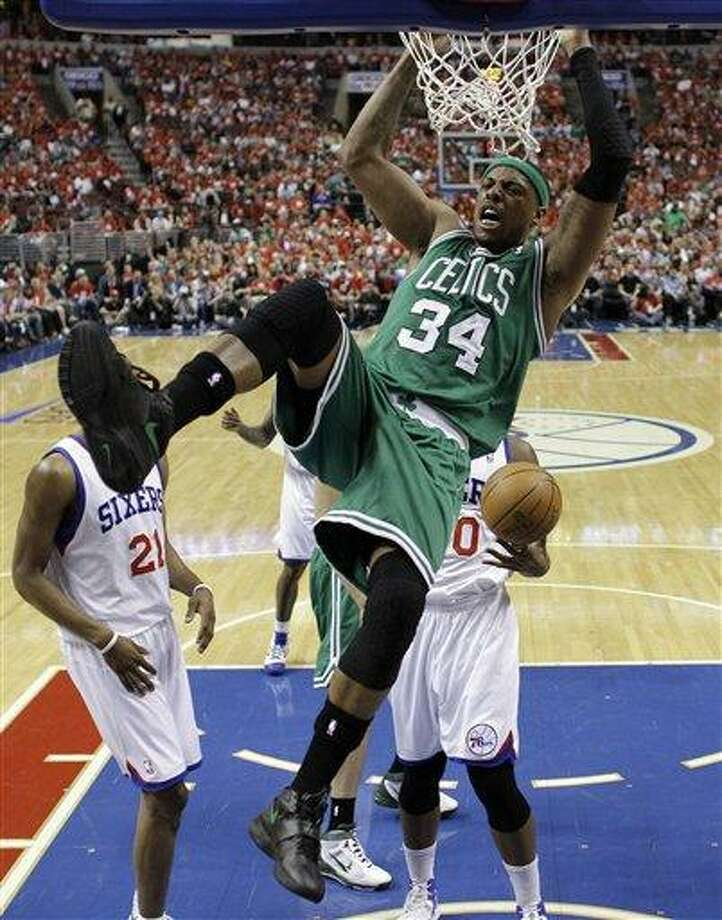 Boston Celtics' Paul Pierce hangs on the rim after a dunk during the first half of Game 3 of an NBA basketball Eastern Conference semifinal playoff series against the Philadelphia 76ers, Wednesday, May 16, 2012, in Philadelphia. (AP Photo/Matt Slocum) Photo: AP / AP