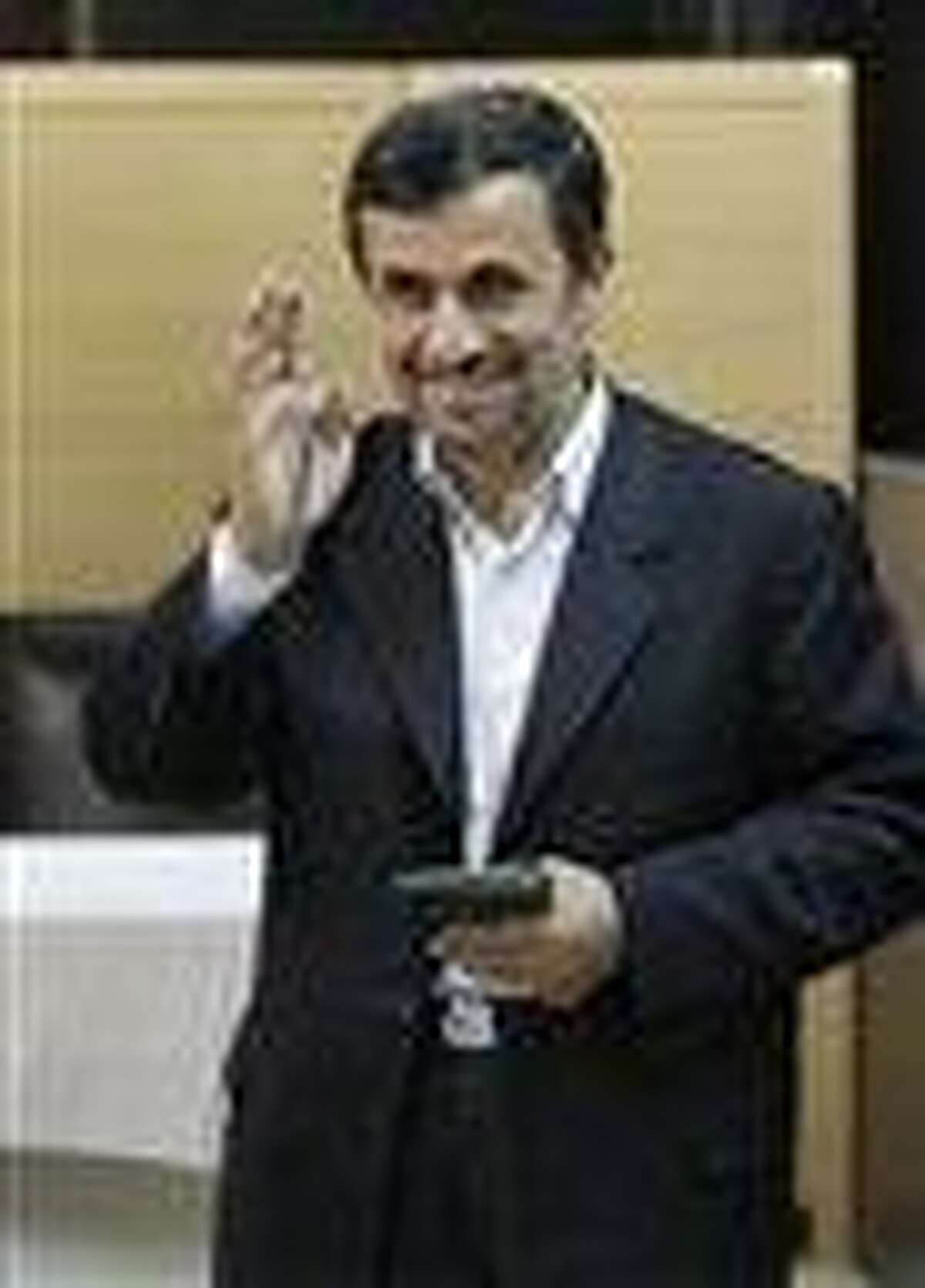 Iranian President Mahmoud Ahmadinejad waves to media after casting his vote for the parliamentary runoff elections at a polling station in Tehran, Iran, Friday. The Iranian leader says he wants to attend the Summer Olympics in London soon, but Britain doesn't want him.
