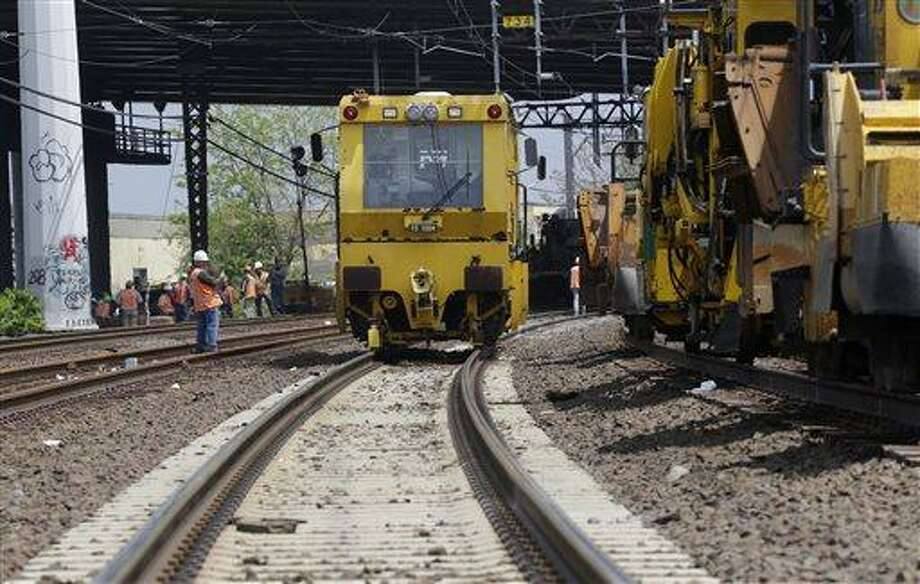 Metro North railroad employees use heavy equipment to repair tracks near Bridgeport, Conn., Monday, May 20, 2013. A train collision on Friday injured 72 people and disrupted rail service into New York City. (AP Photo/Mark Lennihan) Photo: AP / AP