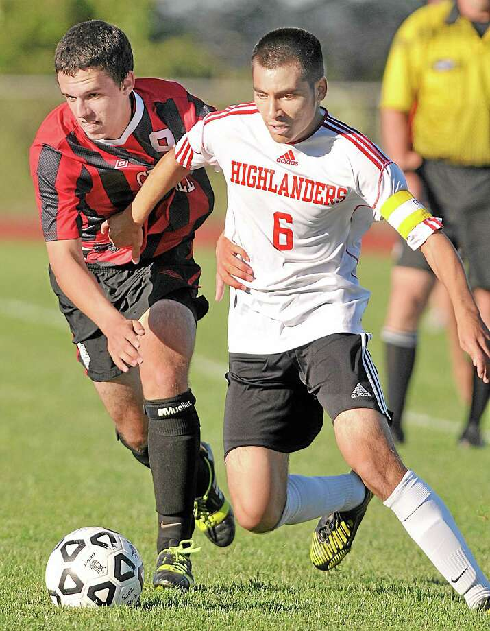 Portland forward captain Abner Velasco battles Cromwell's Derek Parker at midfield Tuesday afternoon. Parker had one goal and one assist leading the Panthers to a 4-0 victory on the road. Photo: Catherine Avalone — The Middletown Press  / TheMiddletownPress