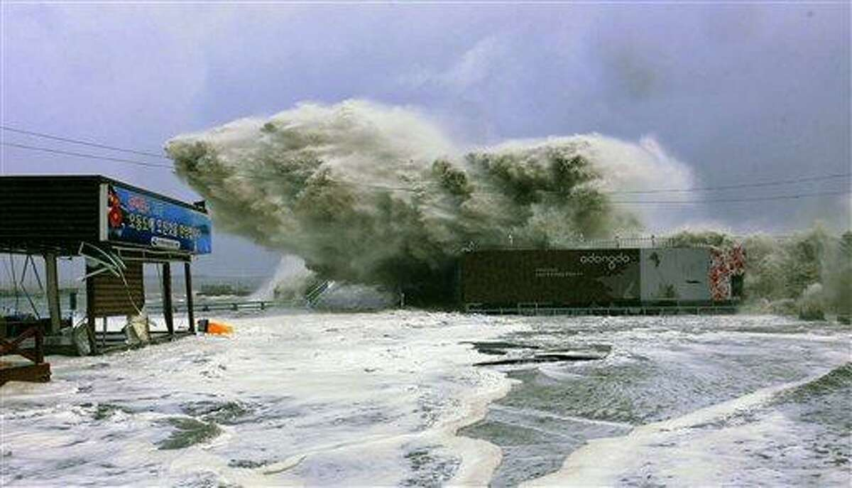 In this photo released by Yeosu City and distributed via Yonhap News Agency, high waves caused by Typhoon Sanba crash on a beach Monday in Yeosu, south of Seoul, South Korea. Associated Press