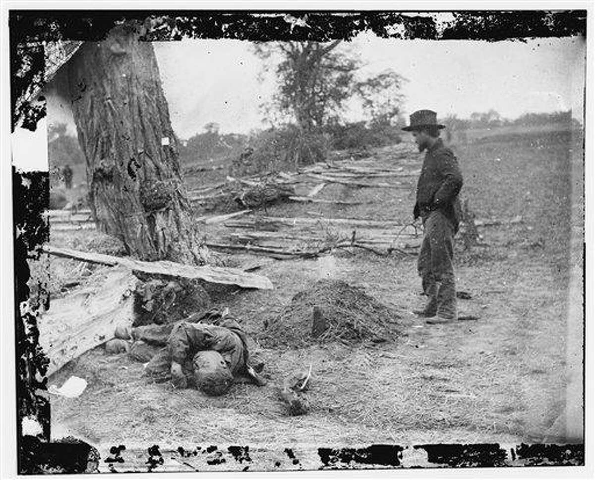 This September 1862 photo provided by the Library of Congress shows a soldier looking upon a Union soldier's grave with the body of a Confederate soldier seemingly tossed aside in Antietam, Maryland. Death is the central theme in the PBS American Experience documentary