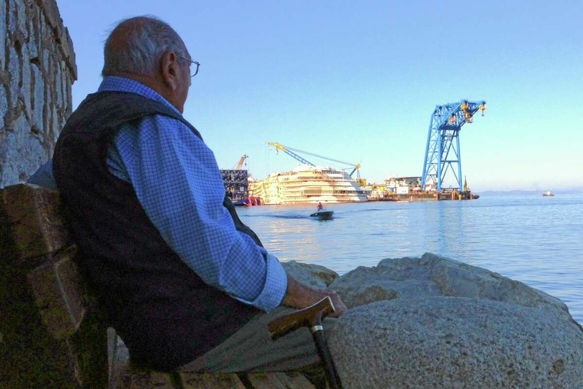 An elderly man watches the Costa Concordia ship as he sits on a bench on the Tuscan Island of Giglio, Italy, Tuesday, Sept. 24, 2013. The trial in Italy of the captain of the shipwrecked Costa Concordia is yielding an unusual alliance of sorts. Both the lawyers for Francesco Schettino and those representing the victims say he is not the only one responsible, and many things went wrong that might have contributed to the death toll when the cruise liner crashed into a reef off a Tuscan island in 2012. On Tuesday both sets of lawyers pressed court-appointed experts about emergency pumps not working after the collision. Thirty-two people died and many others were injured or left traumatized. Schettino is charged with manslaughter, causing the shipwreck and abandoning ship. (AP Photo/Paolo Santalucia)