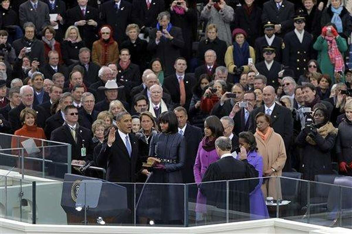 President Barack Obama receives the oath of office from Chief Justice John Roberts as first lady Michelle Obamas and his daughters Malia and Sasha look on at the ceremonial swearing-in at the U.S. Capitol during the 57th Presidential Inauguration in Washington, Monday, Jan. 21, 2013. (AP Photo/Carolyn Kaster)