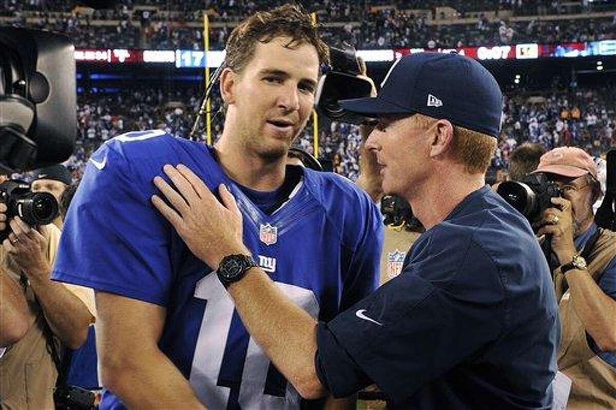 Dallas Cowboys head coach Jason Garrett, right, talks to New York Giants quarterback Eli Manning (10) after an NFL football game, Wednesday, Sept. 5, 2012, in East Rutherford, N.J. The Cowboys won 24-17. (AP Photo/Bill Kostroun)