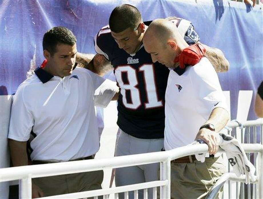 New England Patriots tight end Aaron Hernandez is helped from the field in the first quarter of an NFL football game against the Arizona Cardinals, Sunday, Sept. 16, 2012, in Foxborough, Mass. (AP Photo/Elise Amendola) Photo: AP / AP