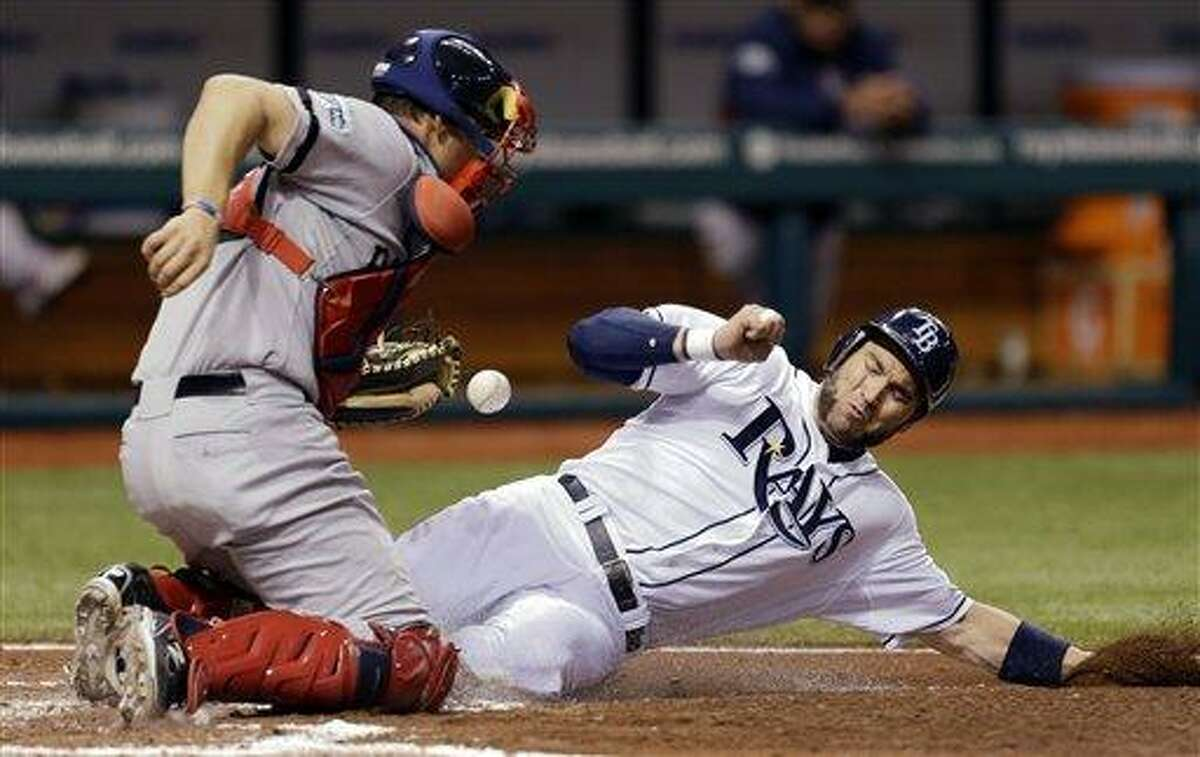 Tampa Bay Rays' Luke Scott, right, scores as Boston Red Sox catcher Ryan Lavarnway can't hang onto the ball on a fifth inning squeeze by Rays' Ryan Roberts off Red Sox pitcher Aaron Cook during a baseball game, Monday, Sept. 17, 2012, in St. Petersburg, Fla. (AP Photo/Chris O'Meara)