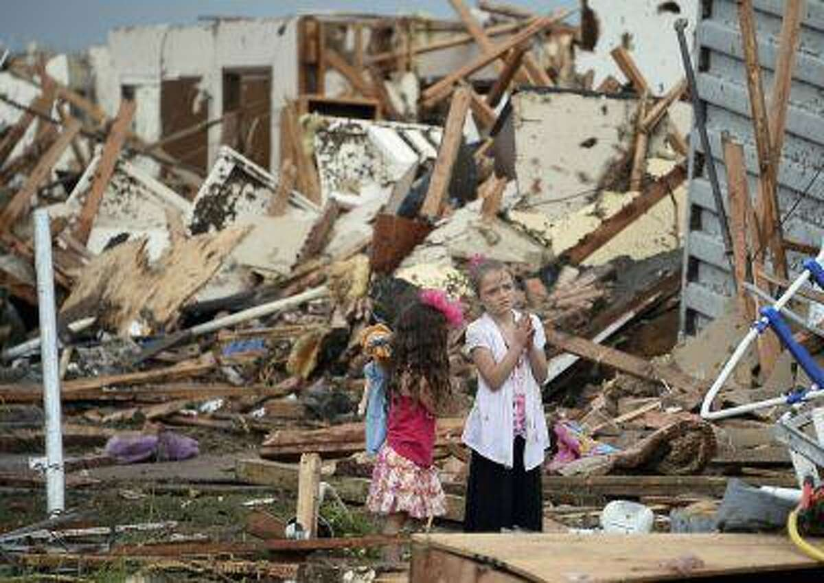 Two girls stand in rubble after a tornado struck Moore, Okla. May 20, 2013.