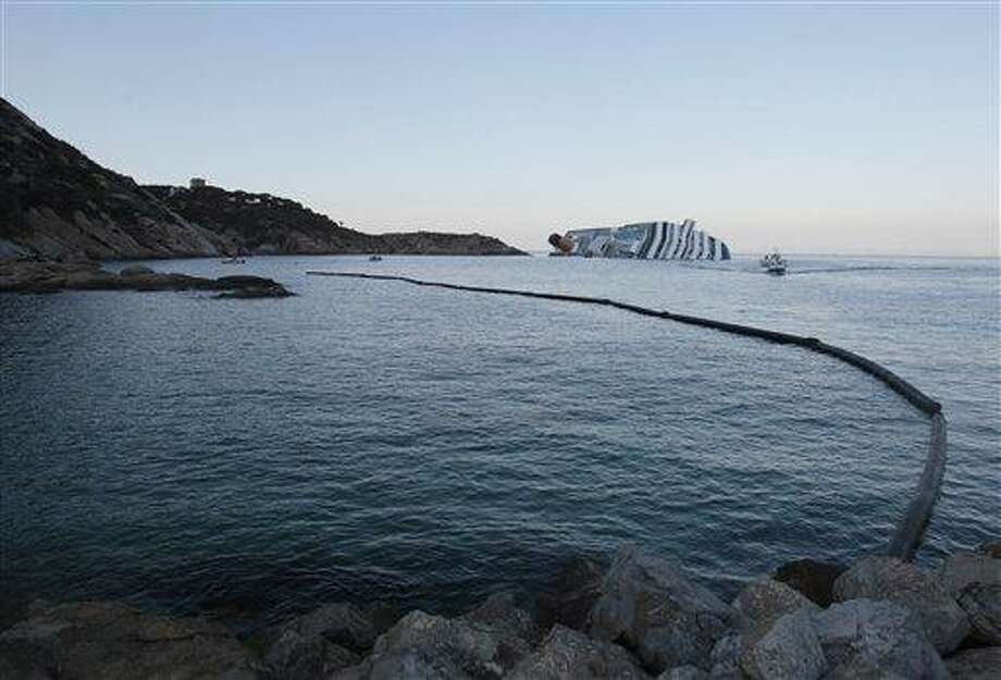 A floating barrier is used Wednesday to contain any eventual oil spill from cruise ship Costa Concordia leaning on its side after running aground the tiny Tuscan island of Giglio, Italy. In response to a question at a press conference in London Wednesday, Italian premier Mario Monti acknowledged concern about a potential leak of 500,000 gallons of fuel aboard the ship. He said authorities had made limiting and preventing leaks a priority, as well as caring for victims.  Associated Press Photo: AP / AP