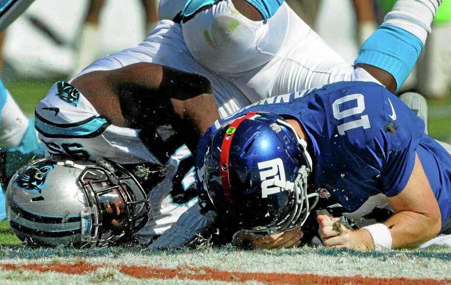 Giants quarterback Eli Manning is sacked by the Panthers' Charles Johnson during Sunday's game. Photo: Mike McCarn — The Associated Press  / FR34342 AP