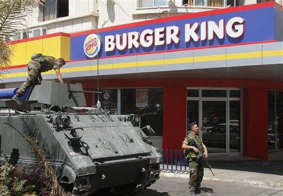 Lebanese army soldiers with their armored personnel carrier, stand guard outside a Burger King as part of stepped up security measures Saturday in the southern port city of Sidon, Lebanon. Angry protesters attacked a Hardees and Kentucky Fried Chicken outlets Friday in Tripoli north Lebanon to protest against a movie that insults Prophet Muhammad. Associated Press