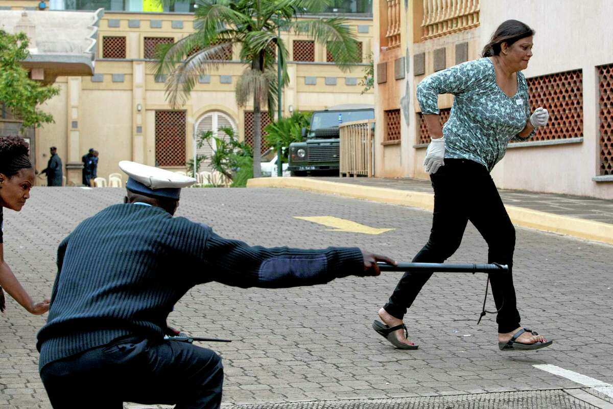 """A paramedic runs for cover outside the Westgate Mall in Nairobi after heavy shooting started Monday, Sept. 23, 2013. Kenya's military launched a major operation at the upscale Nairobi mall and said it had rescued """"most"""" of the hostages being held captive by al-Qaida-linked militants during the standoff. (AP Photo/Sayyid Azim)"""