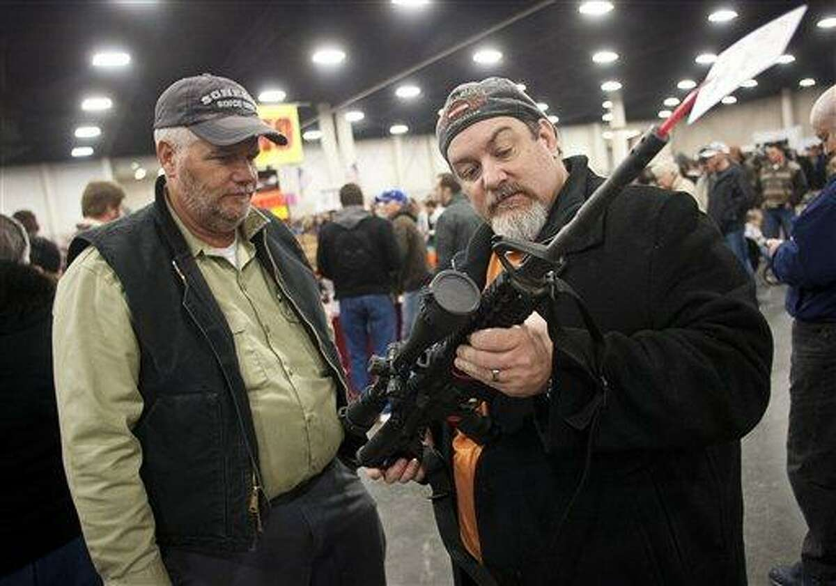 In a Jan. 5, photo, gun owners discuss a potential sale of an AR-15, during the 2013 Rocky Mountain Gun Show at the South Towne Expo Center in Sandy, Utah. AP Photo/The Deseret News, Ben Brewer, File