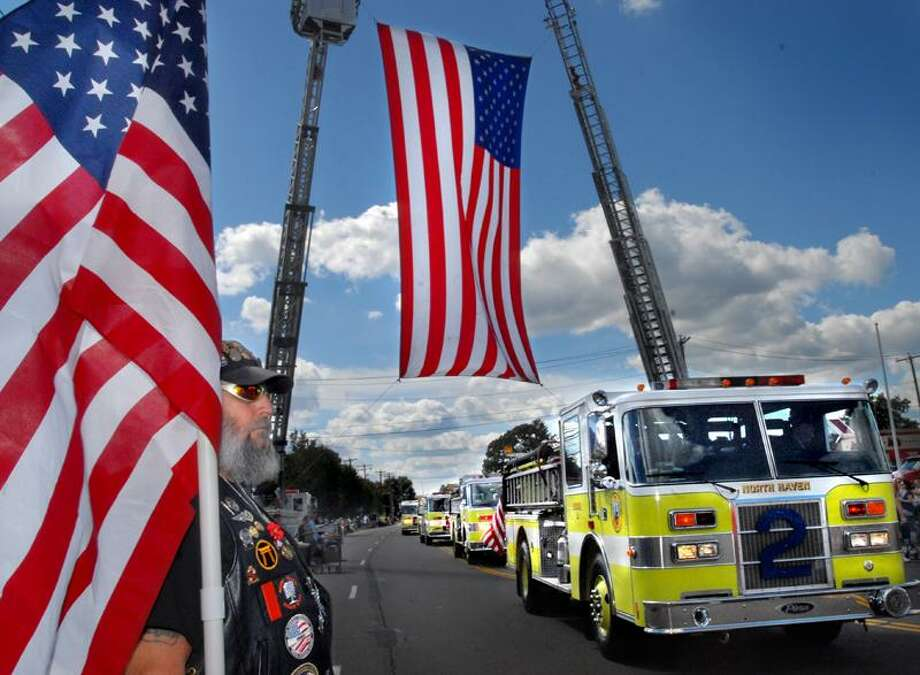 Army veteran, Lou Guarino, of the Ct. Patriot Guard, holds the American Flag on the final section of the Connecticut State Firefighters Convention Parade route. Guarino is from Higganum.  Melanie Stengel/Register