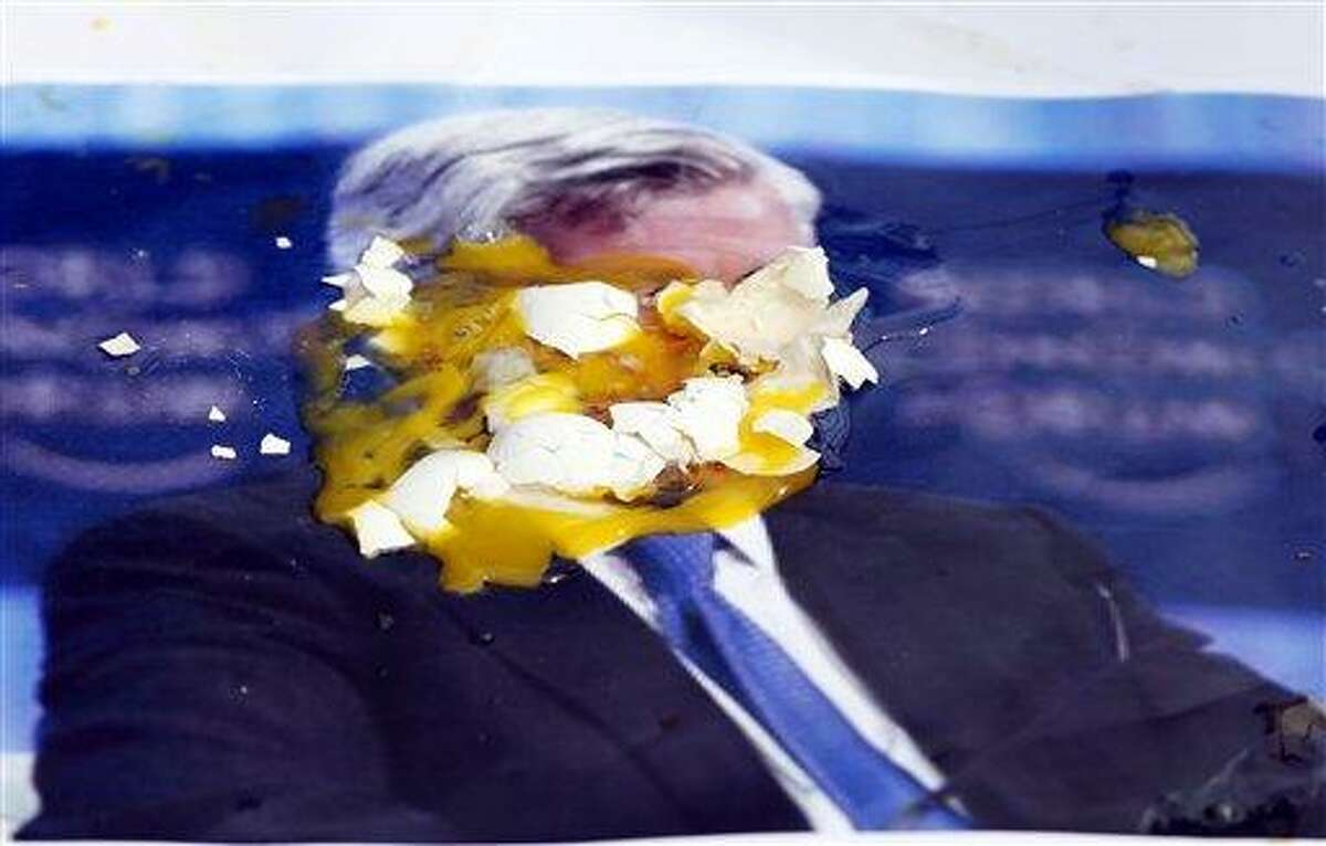 A poster of JPMorgan Chase CEO Jamie Dimon is covered with eggs thrown by protesters, outside the gate of the JPMorgan Chase annual stockholders meeting Tuesday in Tampa, Fla. Associated Press