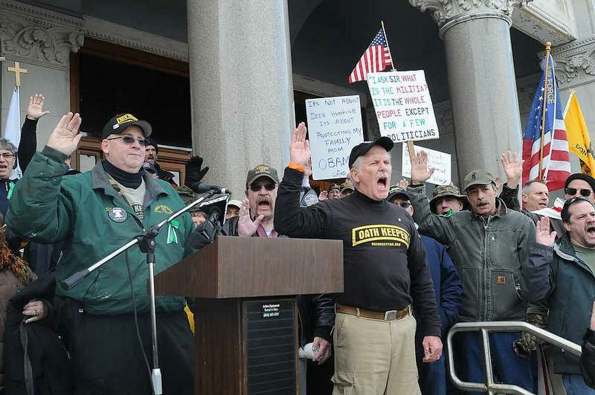 Firearms advocates take the Constitutional Oath lead by Oath Keepers Connecticut Chapter president John Beidler of Southington, Conn., at right of podium, as they demonstrate on the steps of the state Capitol in Hartford during the first national Guns Across America Rally and Gun Appreciation Day SaturdayJanuary 19, 2013. Photo by Peter Hvizdak / New Haven Register