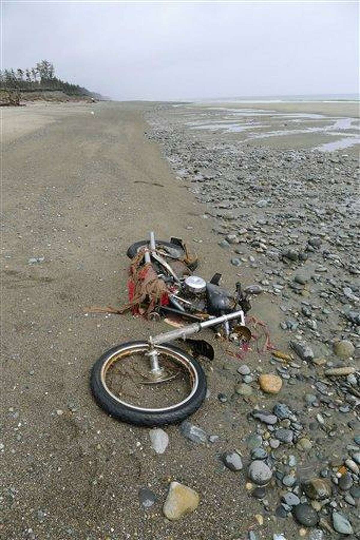 In this photo taken by Canadian Peter Mark at the end of April, a Harley-Davidson motorbike lies on a beach in Graham Island, western Canada. Japanese media say the motorcycle lost in last year's tsunami washed up on the island about 6,400 kilometers (4,000 miles) away. The rusted bike was originally found by Mark in a large white container where its owner, Ikuo Yokoyama, had kept it. The container was later washed away, leaving the motorbike half-buried in the sand. Yokoyama, who lost three members of his family in the March 11, 2011, tsunami, was located through the license plate number, Fuji TV reported. Associated Press