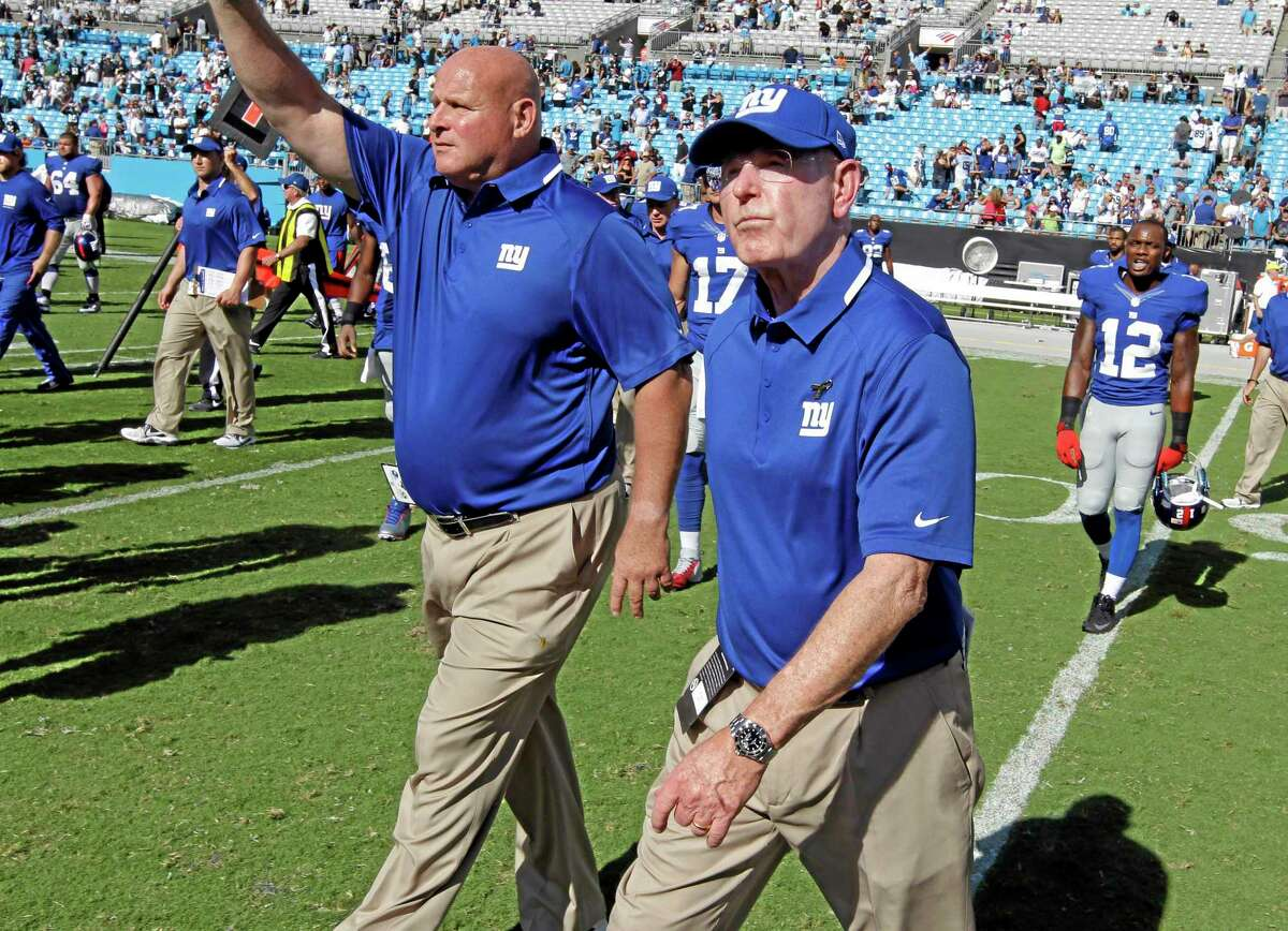 Giants head coach Tom Coughlin, front right, walks off the field after Sunday's loss to the Panthers.