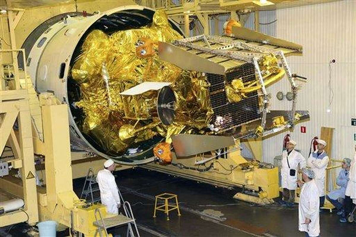 In this Nov. 2, 2011, file photo, distributed by Russian Roscosmos space agency, technicians work on the Phobos-Ground probe at Baikonur, Kazakhstan. The spacecraft has since failed and is breaking up and falling to earth. Associated Press