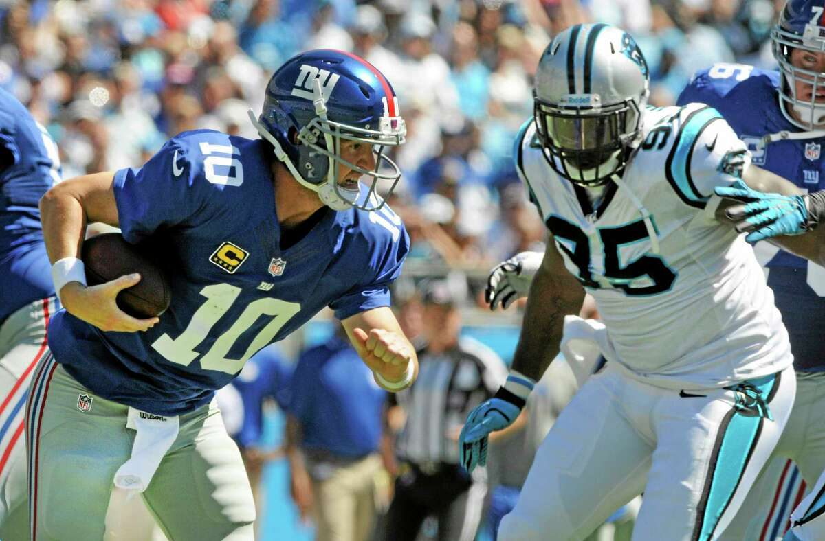Giants quarterback Eli Manning tries to escape the tackle of Panthers defensive end Charles Johnson during the first half Sunday. Manning was sacked on the play.