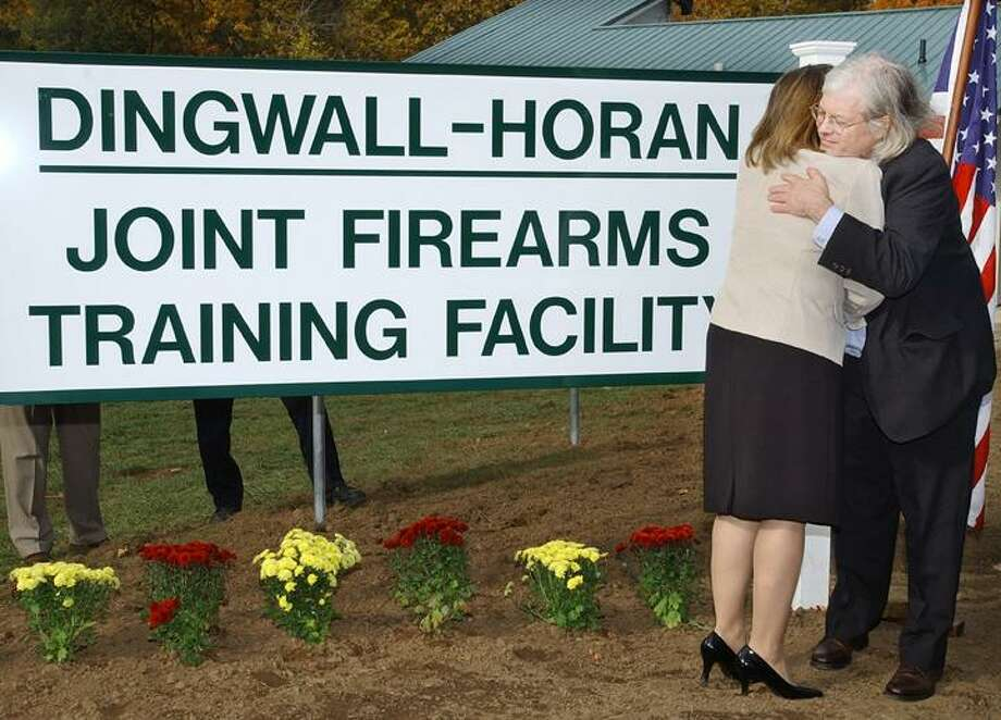 Catherine Avalone/The Middletown Press Kimberly Dingwall, wife of the late Sgt. Georg R. Dingwall, and Richard Horan, son of FBI Special Agent Richard P. Horan, embrace during the dedication of the Dingwall-Horan Joint Firearms Training Facility in Middletown in this 2009 file photo.