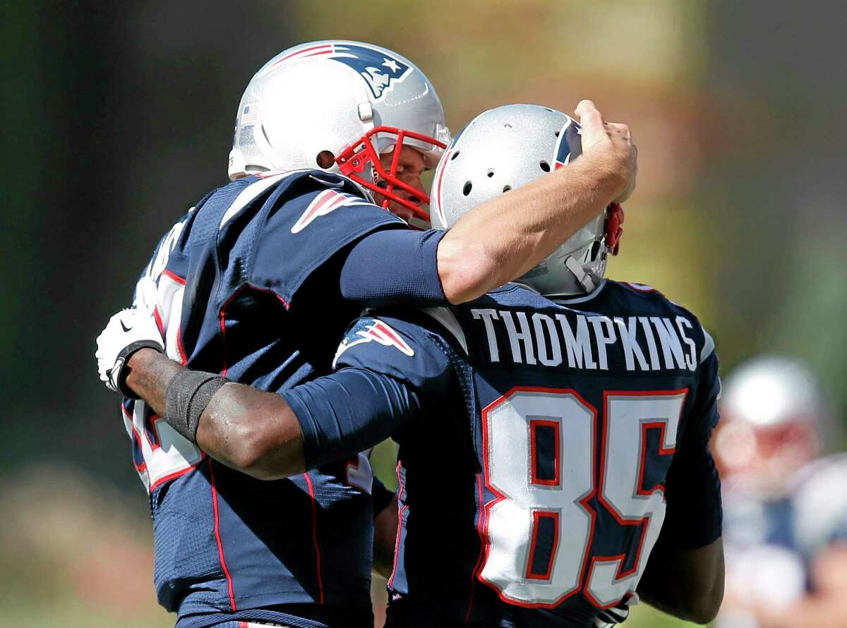 Patriots quarterback Tom Brady, left, celebrates his touchdown pass to wide receiver Kenbrell Thompkins in the first half Sunday.