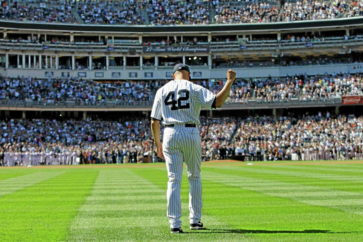 Mariano Rivera salutes the crowd as he walks in from the bullpen during Sunday's ceremony.
