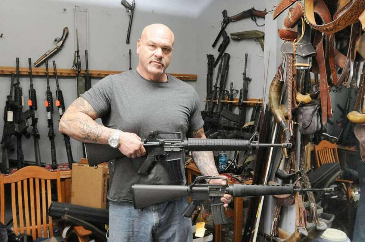 """Thomas Imperati, owner of the The Hunter's Shop in Branford, Conn. compares two AR-15 in his gun shop Saturday, January 05, 2013. The AR-15, top, is considered a legal semi-automatic rifle in Connecticut and the AR-15 below is not legal in Connecticut. The """"illegal"""" rifle on the bottom has a bayonet lug for attaching a bayonet and and includes a flash hider on the front of the muzzle and the """"legal"""" AR-15 has a muzzle break (or recoil compensator) on the front and does not have a bayonet lug. Folding and collapsing stocks on AR-15's are also illegal in Connecticut. Photo by Peter Hvizdak / New Haven Register"""