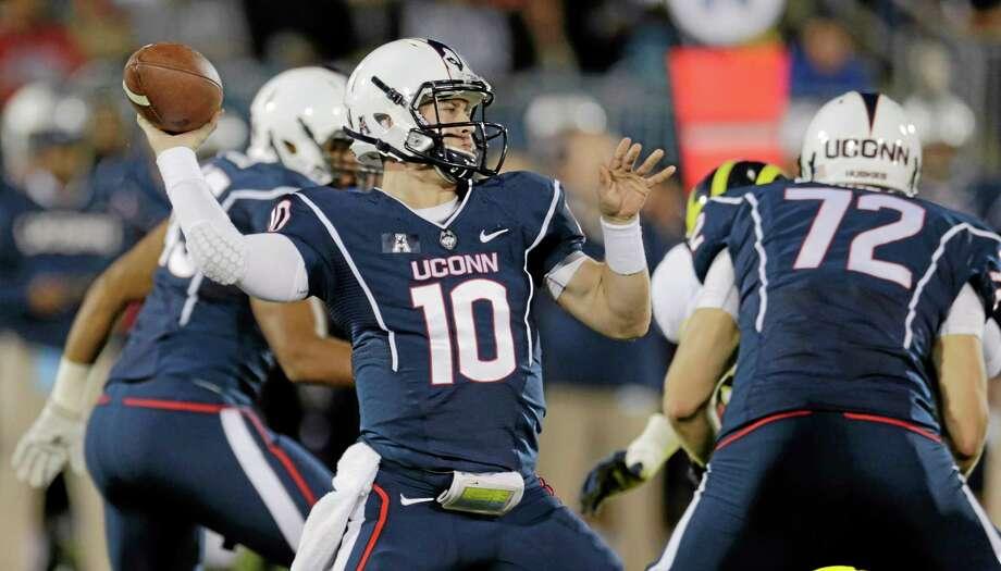 UConn quarterback Chandler Whitmer throws against Michigan during the first quarter Saturday night. Photo: Charles Krupa — The Associated Press  / AP