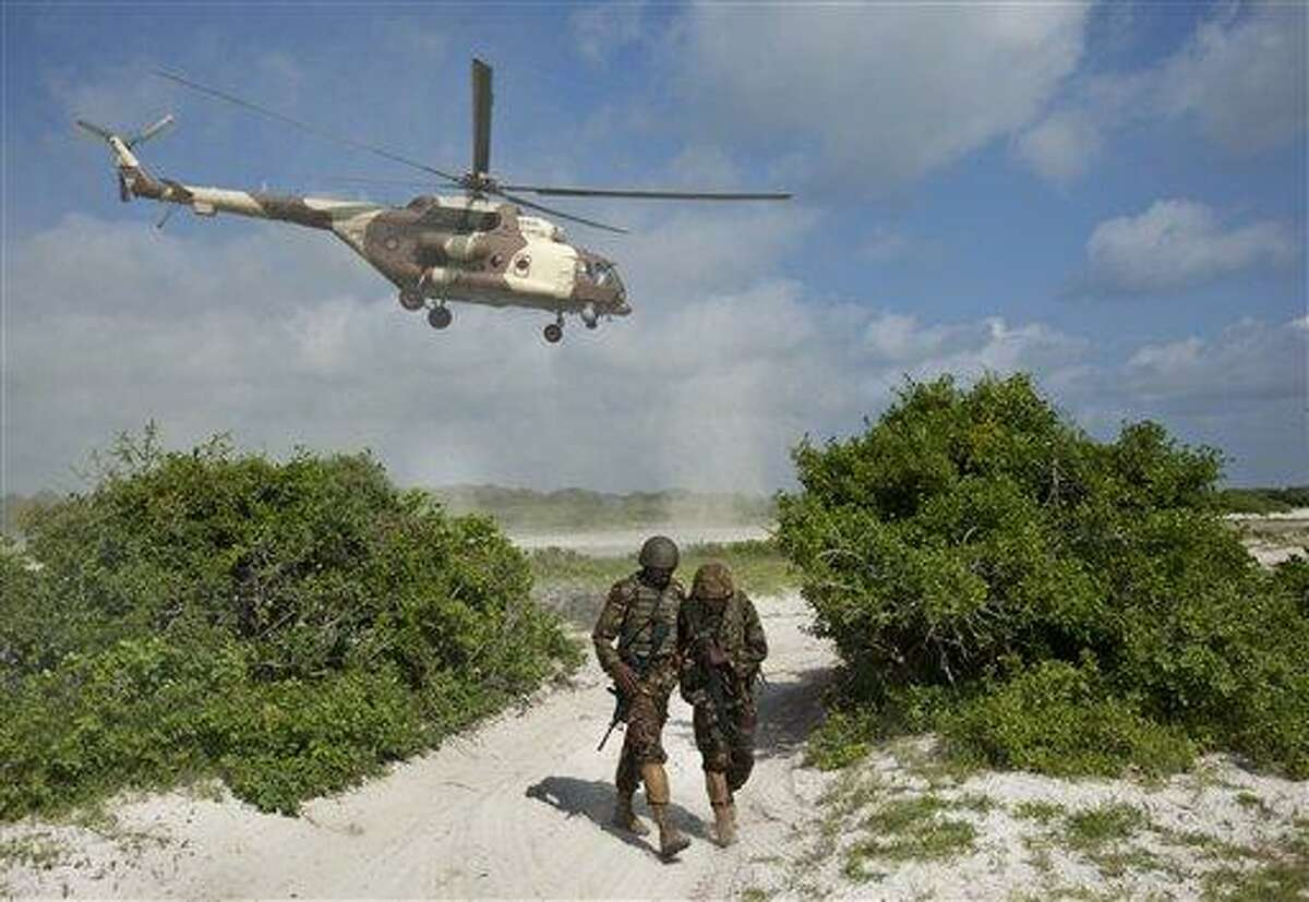 In this December 2011 file photo, two Kenyan army soldiers shield themselves from the downdraft of a Kenyan air force helicopter as it flies away from their base near the seaside town of Bur Garbo, Somalia. Kenyan fightr jets have been accused of accidentally killing five Somali children. Associated Press