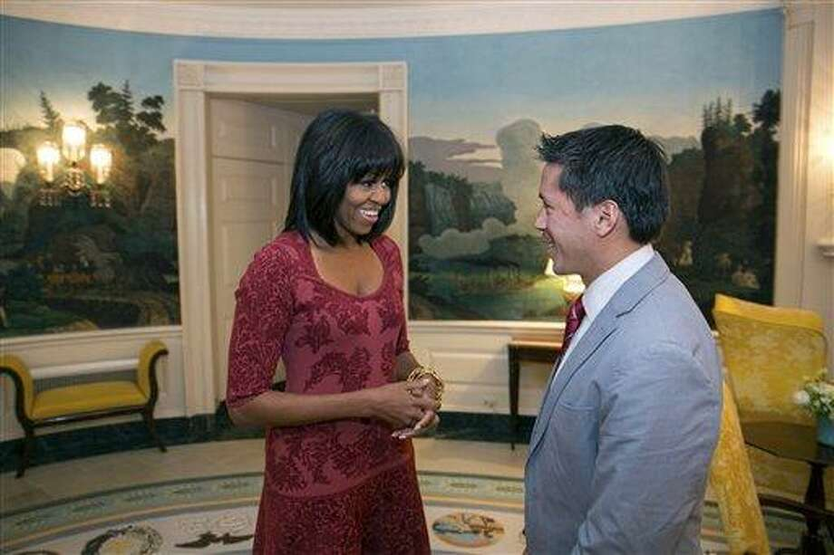 In this image released by the White House, first lady Michelle Obama greets David Hall, one of eight citizen co-chairs for the Inauguration, in the Diplomatic Reception Room of the White House in Washington, Thursday. The photo is showing something different about Obama - bangs in her hair. AP Photo/The White House, Lawrence Jackson Photo: AP / The White House