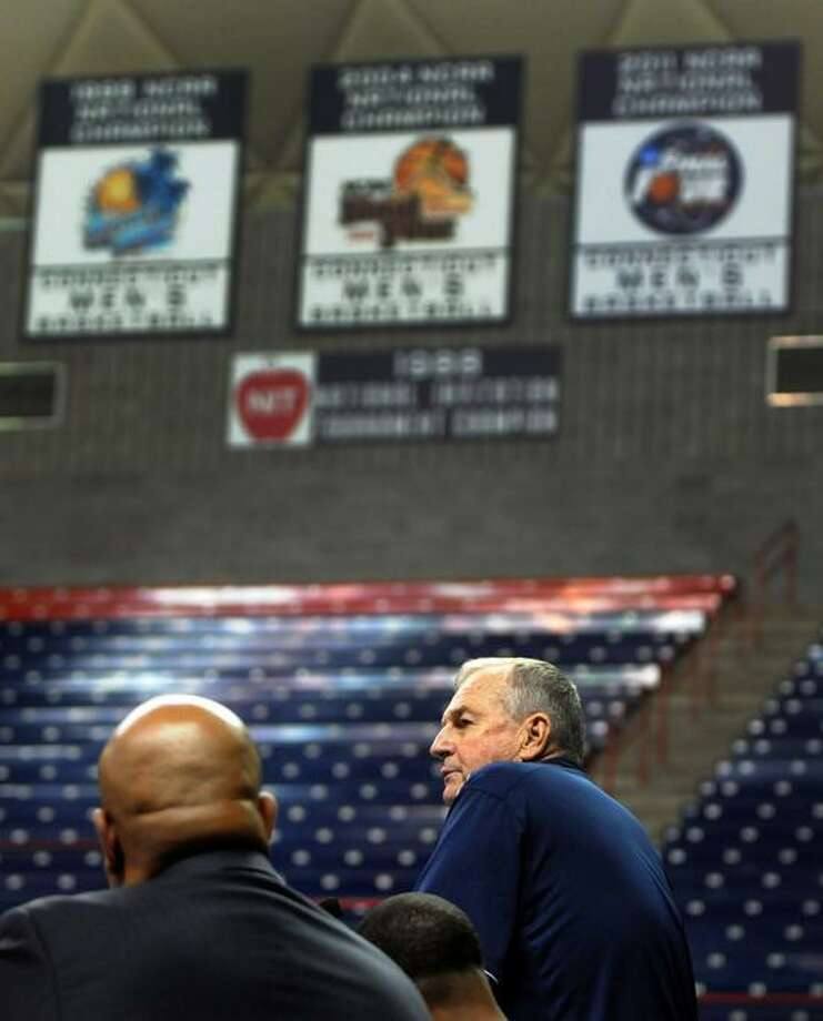 With three NCAA national championship banners hanging from the ceiling of Gampel Pavilion that were won under his tutelage, University of Connecticut Men's Basketball coach Jim Calhoun announces his retirement during a press conference September 13, 2012 at  Gampel Pavilion on UConn's main campus in Storrs, Connecticut. Sitting next to Calhoun are Warde Manuel UConn Director of Athletics, left, and new UConn basketball coach Kevin Ollie, second from left. Photo by Peter Hvizdak / New Haven Register Photo: New Haven Register / ©Peter Hvizdak /  New Haven Register