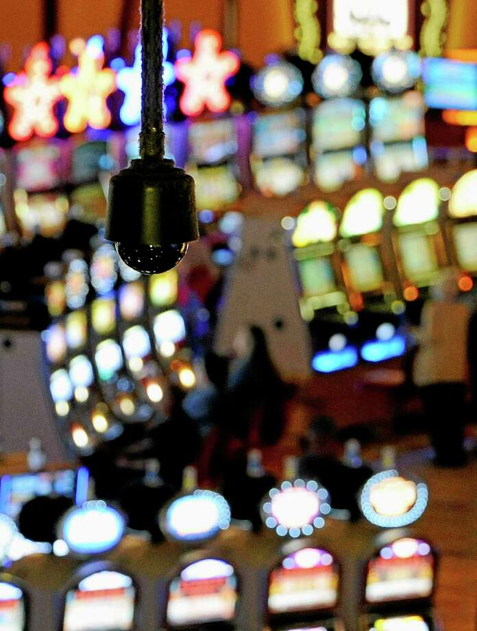 In this Sept. 18, 2013, photo, a security camera hangs above slot machines at Mohegan Sun in Uncasville, Conn. As table games spread across the Northeast, resorts are using their own intelligence network more than ever to stay ahead of suspect players _ professional thieves as well as card counters _ who can easily hit multiple casinos in the span of a few days. (AP Photo/Jessica Hill) Photo: AP / FR125654 AP