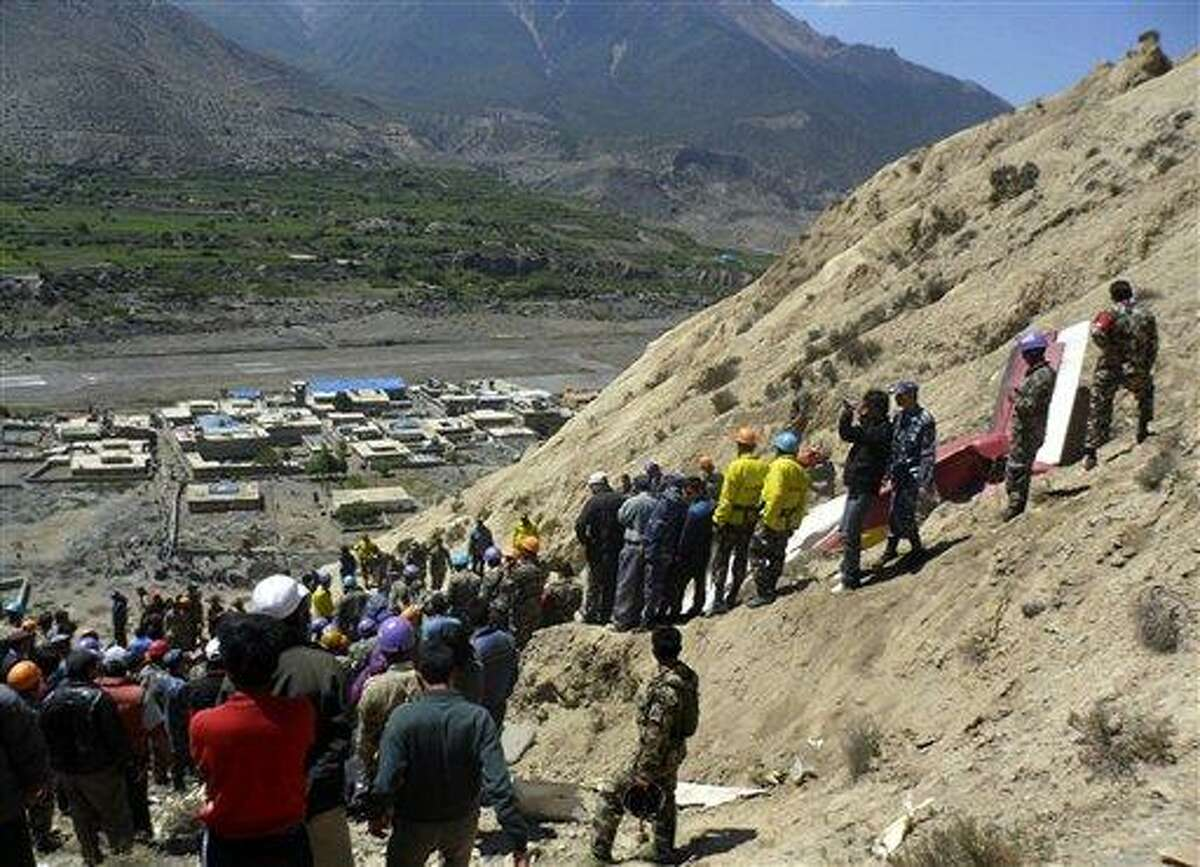 Nepalese rescue workers and officials inspect the site of a plane crash Monday near Jomsom, 125 miles northwest of the capital, Katmandu, Nepal. The plane crashed into a mountain in the Himalayas while trying to land at an airport in northern Nepal on Monday, killing 15 people and critically injuring six. Associated Press