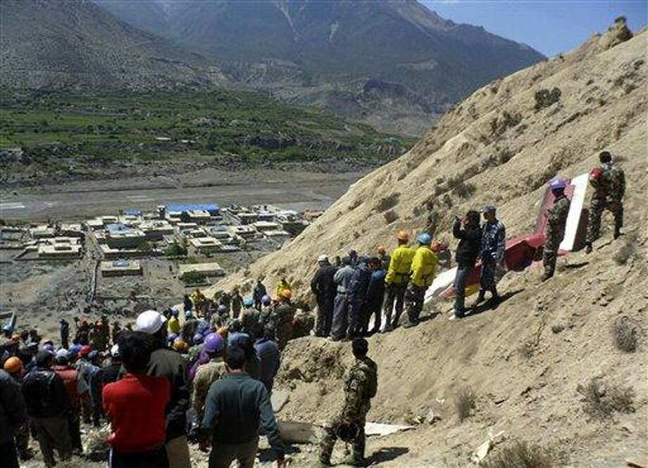 Nepalese rescue workers and officials inspect the site of a plane crash Monday near Jomsom, 125 miles northwest of the capital, Katmandu, Nepal. The plane crashed into a mountain in the Himalayas while trying to land at an airport in northern Nepal on Monday, killing 15 people and critically injuring six. Associated Press Photo: AP / AP