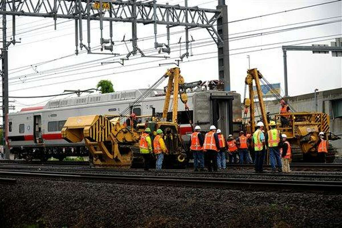 A derailed Metro-North rail car is hoisted back on to the tracks in Bridgeport. Conn. on Sunday, May 19, 2013. Crews will spend days rebuilding 2,000 feet of track, overhead wires and signals following the collision between two trains Friday evening that injured 72 people, Metro-North President Howard Permut said Sunday. (AP Photo/The Connecticut Post,Brian A. Pounds)